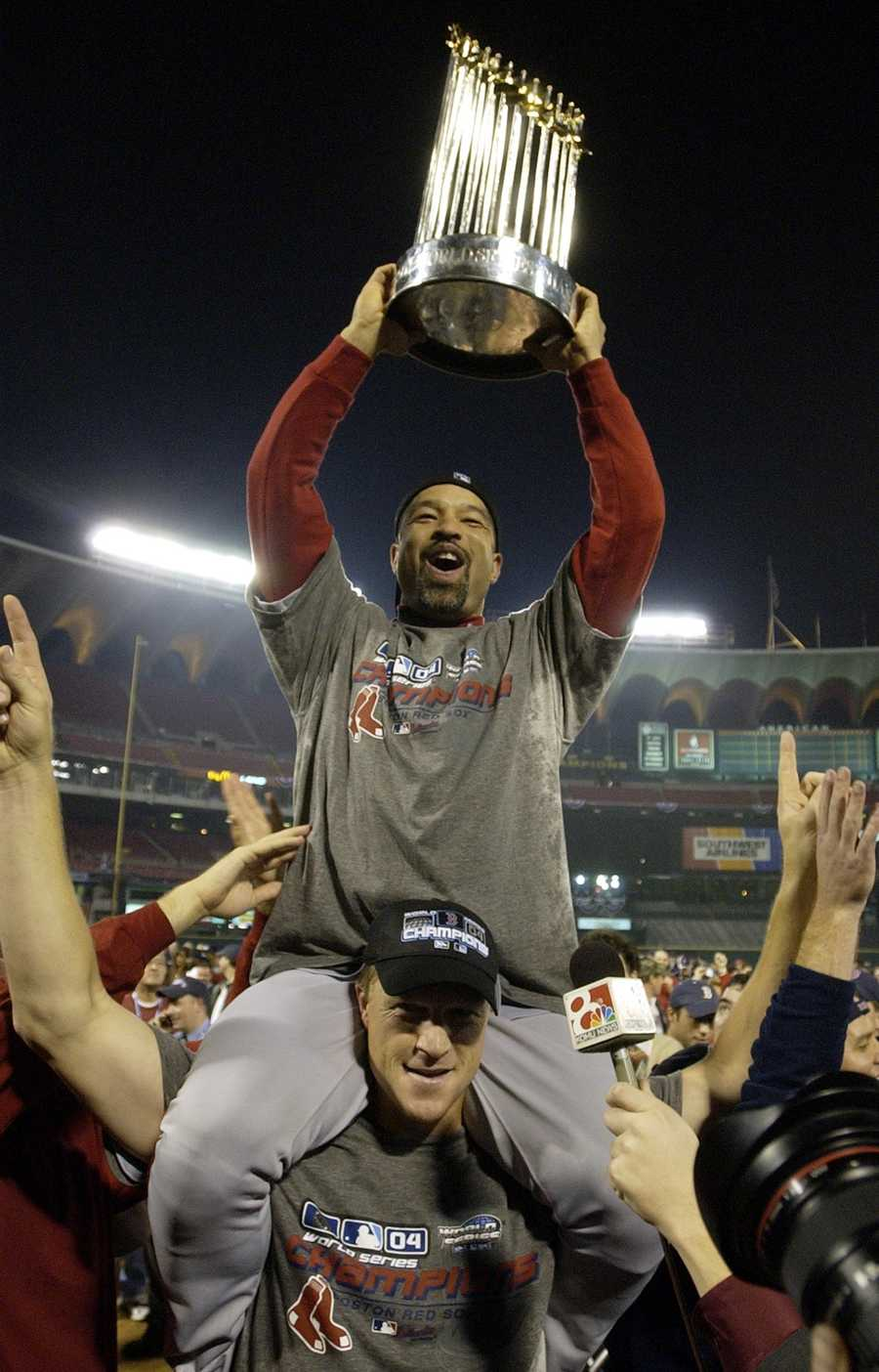 Boston Red Sox's Dave Roberts hoists the World Series trophy while riding the shoulders of pitcher Mike Timlin after winning the World Series with a 3-0 win over the St. Louis Cardinals in Game 4 of the World Series Wednesday, Oct. 27, 2004, in St. Louis.
