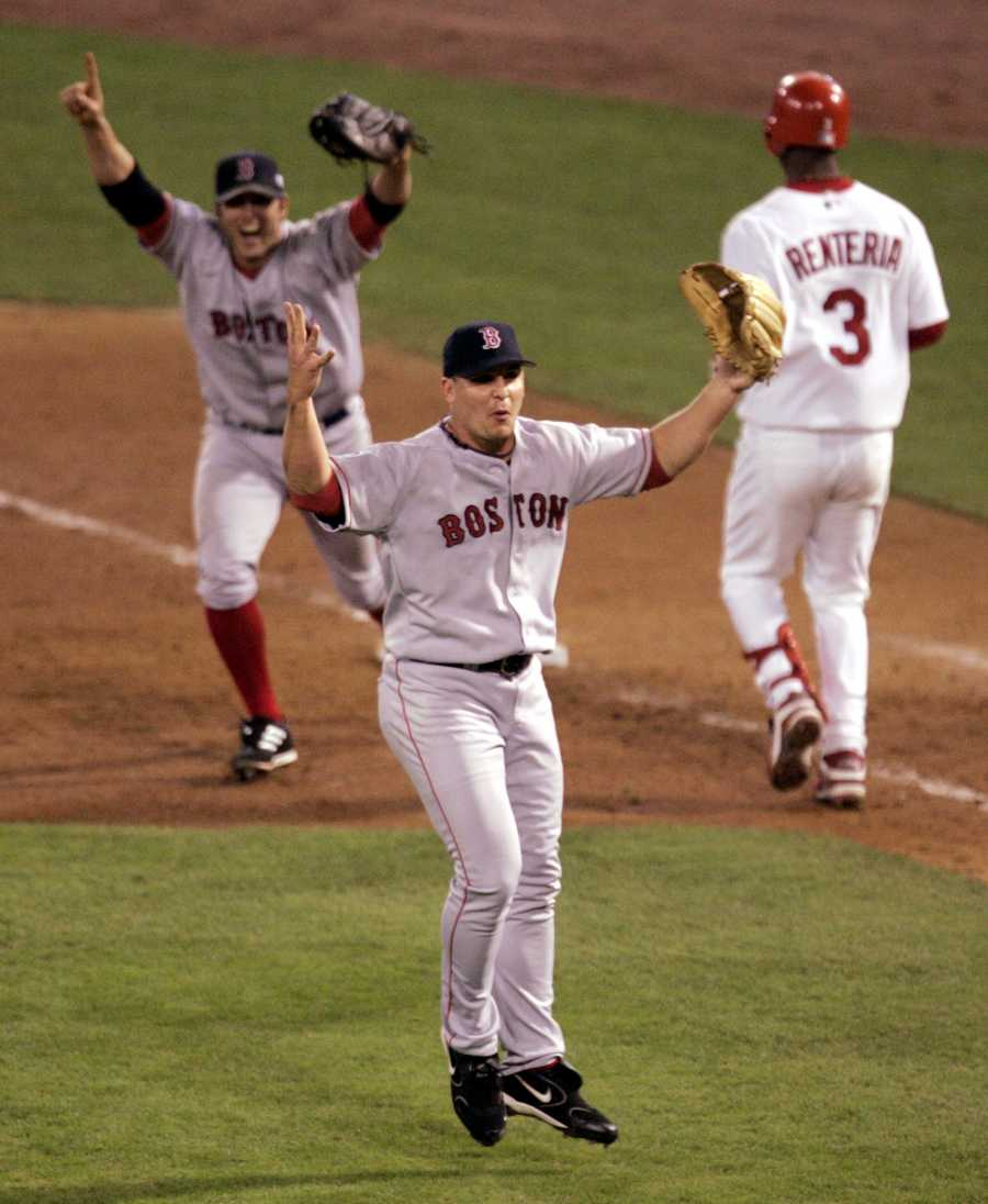 Boston Red Sox pitcher Keith Foulke, center, and first baseman Doug Mientkiewicz, left, celebrate after St. Louis Cardinals' Edgar Renteria (3) grounded out to end the ninth inning and give Boston a 3-0 win and a sweep of the World Series, Wednesday Oct. 27, 2004, in St. Louis.