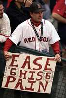 Boston fan Fred Forsgard, from Marblehead, Mass. watches batting practice before Game 4 of the World Series between the Boston Red Sox and St. Louis Cardinals, Oct. 27, 2004, in St. Louis. Before 2004, the Sox had not won a World Series in 86 years.