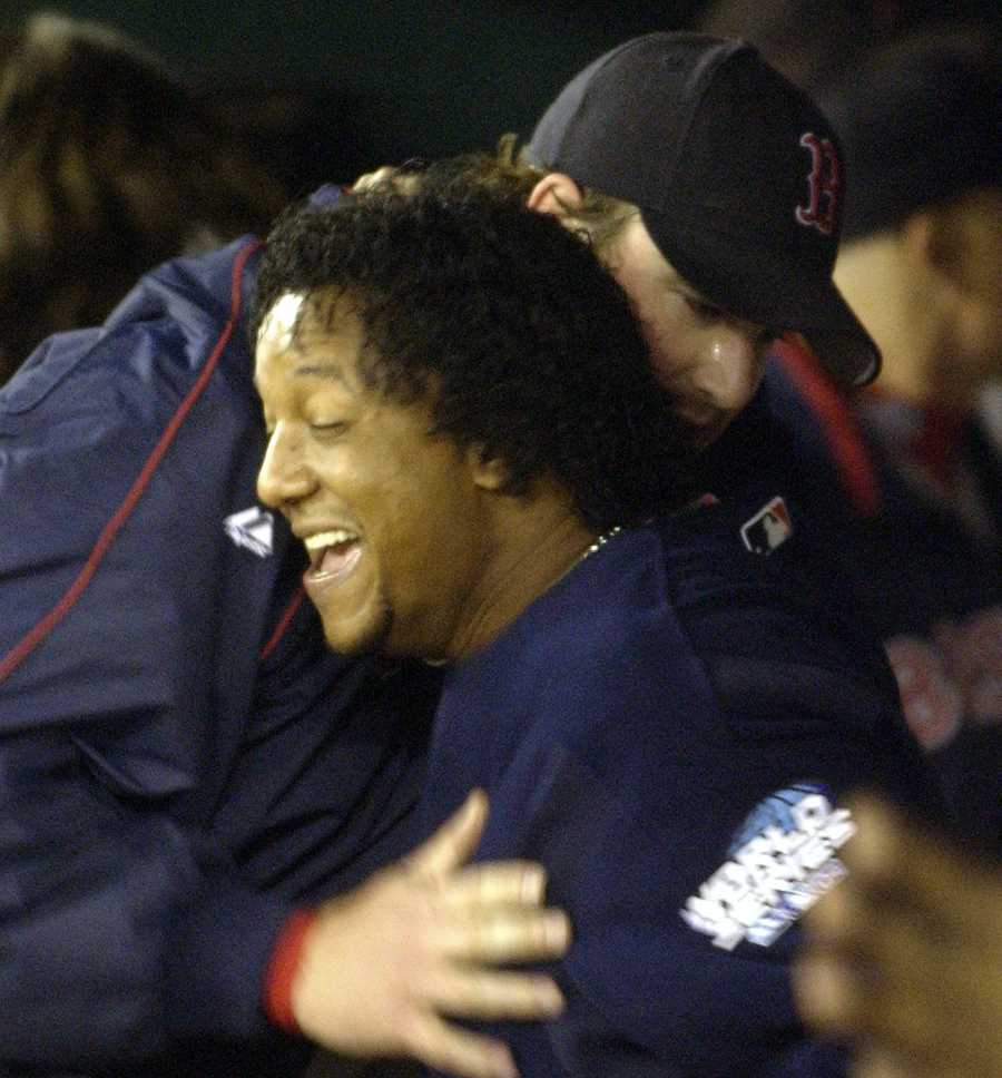 Boston Red Sox pitcher Pedro Martinez, foreground, hugs teammate Derek Lowe in the dugout after the seventh inning of Game 4 of the World Series against the St. Louis Cardinals Wednesday, Oct. 27, 2004, in St. Louis.