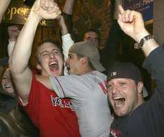 Boston Red Sox fans celebrate in the street near Fenway Park in Boston after the Red Sox beat the St. Louis Cardinals in the World Series, Wednesday, Oct. 27, 2004.