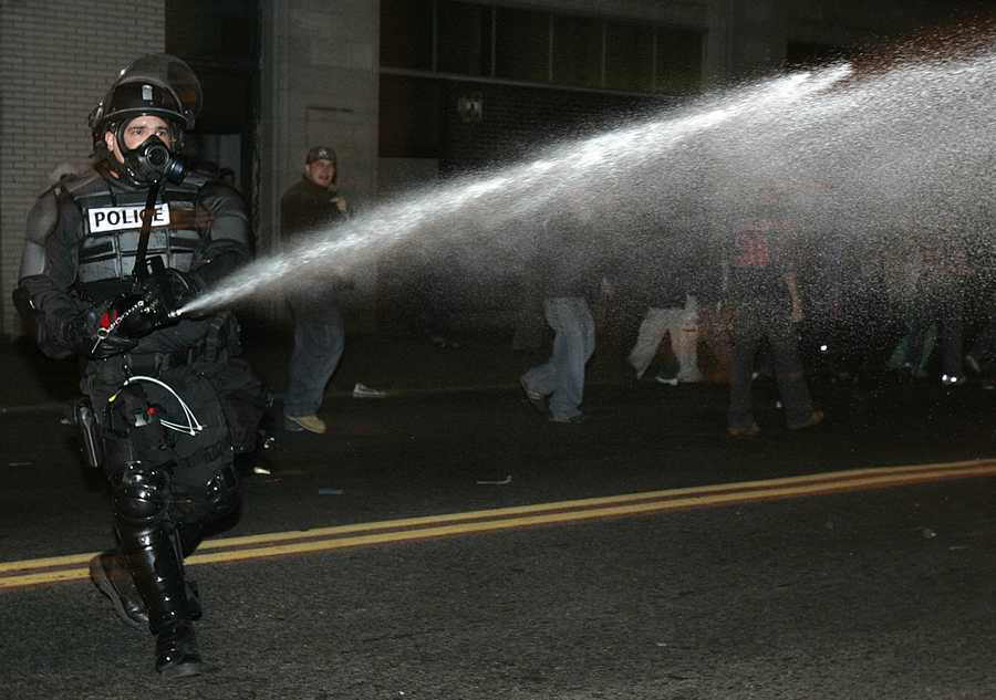 A policeman in riot gear disperses the crowd with pepper spray outside Fenway Park in Boston as they celebrate after the Red Sox beat the St. Louis Cardinals to win the World Series Wednesday, Oct. 27, 2004. .