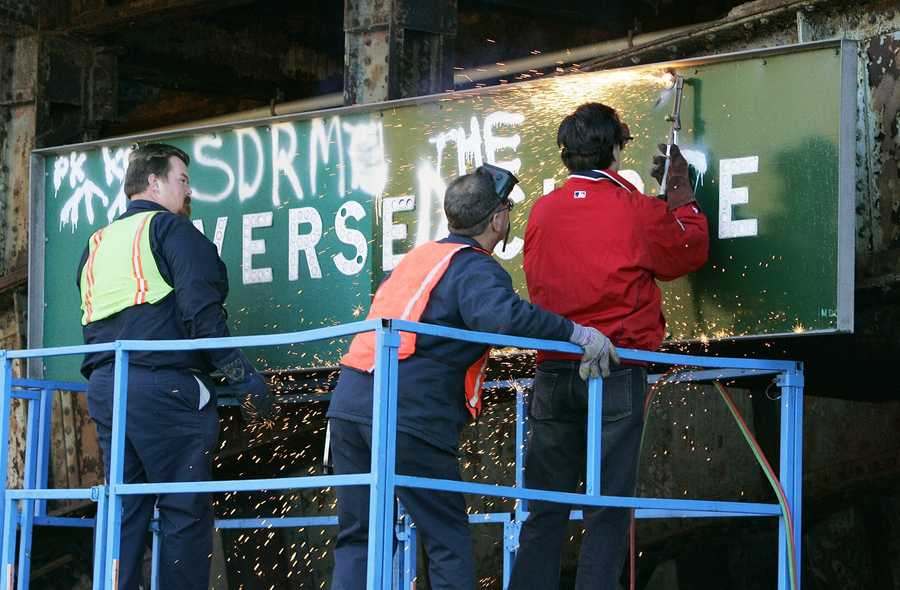 """Massachusetts Gov. Mitt Romney, right, uses a blowtorch to cut and remove a """"Reverse Curve"""" traffic sign from the Longfellow Bridge over Storrow Drive in Boston Thursday, Oct. 28, 2004, which had been defaced to read """"Reversed the Curse"""" in the wake of the Boston Red Sox World Series victory. Graffiti artists have been defacing the sign for the past 33 years of Red Sox history."""
