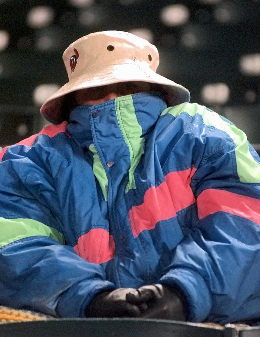 Baltna Snowden, of Wooster, Ohio, is bundled up from the cold as she waits for the start of Game 4 of the World Series at Cleveland's Jacobs Field, Wednesday, Oct. 22, 1997. Temperatures at game time were in the 30s with snow flurries.