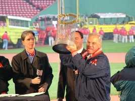 Boston Mayor Thomas Menino holds the World Series trophy as Red Sox principal owner John Henry looks on.