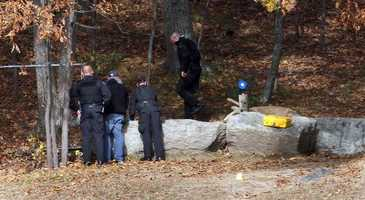 Crime scene investigators look over a stone wall near where the body of teacher Colleen Ritzer was found Wednesday morning Oct. 23.