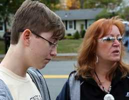 Gail Wade and her son Danvers High student Spencer Wade talk about teacher Colleen Ritzer in front of the school at a make-shift memorial they have set up