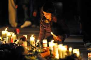 Hana Rhaddaoui, 7, from Danvers, helps to keep candles lit during a candle light vigil held outside the Danvers High School for Danvers High School math teacher Colleen Ritzer who was murdered by one of her students, 14 year old Philip D. Chism.