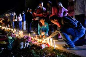 Danvers school students Isabella Burrell, 8th grade, and Colin Marie, junior, light a candle at a memorial outside the high school during a candle light vigil held for Danvers High School math teacher Colleen Ritzer who was murdered by one of her students, 14 year old Philip D. Chism.