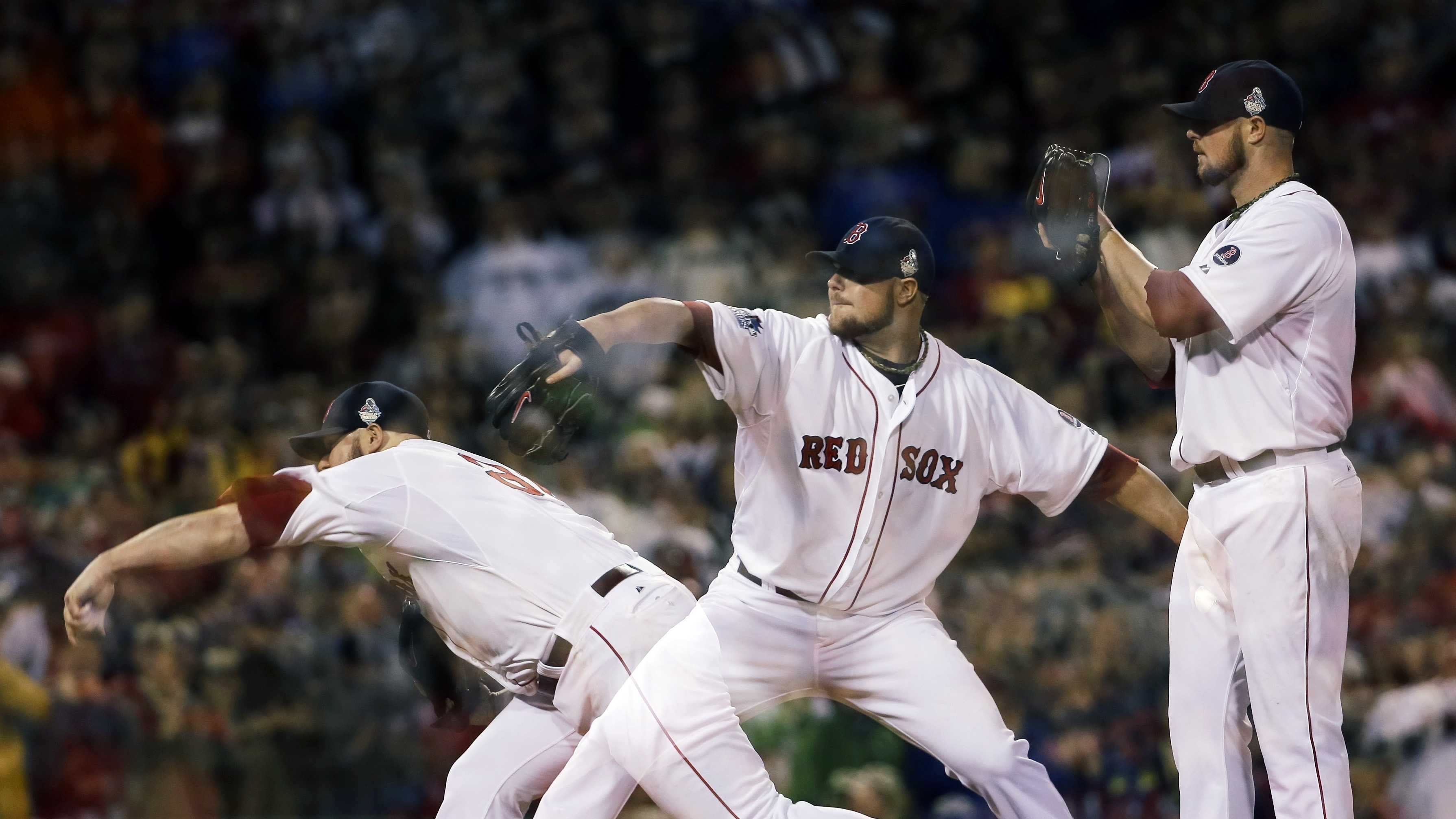 This multiple exposure image shows Boston Red Sox starting pitcher Jon Lester throwing during the seventh inning of Game 1 of baseball's World Series against the St. Louis Cardinals Wednesday, Oct. 23, 2013, in Boston.