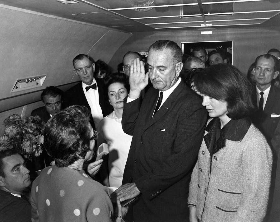 Judge Sarah T. Hughes administers the Presidential Oath of Office to Lyndon Baines Johnson aboard Air Force One, at Love Field, Dallas Texas. Mrs. Johnson, Mrs. Kennedy, Jack Valenti, Cong. Albert Thomas, Cong. Jack Brooks, Associate Press Secretary Malcolm Kilduff (holding microphone) and others witness.