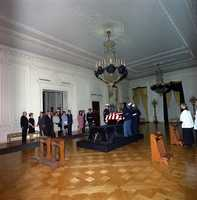 The honor guard places President Kennedy's casket in the East Room, 23 November 1963. Those watching include Hugh Auchincloss, Janet Auchincloss, Kenneth O'Donnell, Larry O'Brien, Secretary of Defense Robert McNamara, Naval Aide Captain Tazewell Shepard, Jean Kennedy Smith, Sargent Shriver, Jacqueline Kennedy, Attorney General Robert Kennedy, and others.