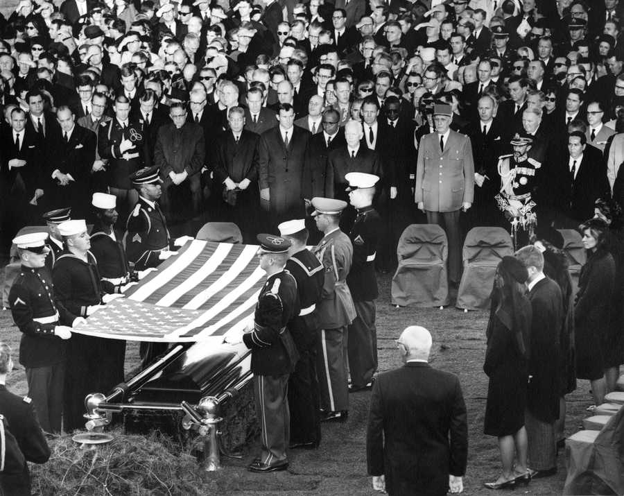 Burial and folding of the flag ceremony for President John F. Kennedy, 25 November 1963.  Photograph includes: (right side, front to back) Jacqueline Kennedy, Robert F. Kennedy, Eunice Shriver, Patricia Lawford, Jean Smith, Super of the Arlington National Cemetary Jack Meltzer, (front row middle to right) President of West Germany Heinrich Luebbe, General Charles de Gaulle of France, Emperor of Ethiopia Haile Selassie, President of the Phillipines Diosdado Macapagal, and mourners. Gravesite, Arlington National Cemetary, Washington, D.C.