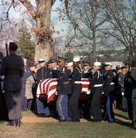 Burial Service for President John F. Kennedy at Arlington National Cemetery with pallbearers carrying the casket to the grave, 25 November 1963.