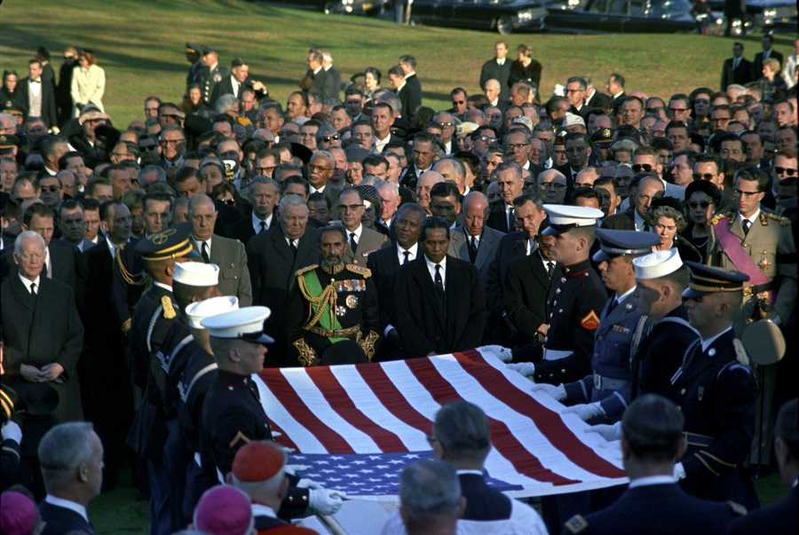 Burial Service for President John F. Kennedy at Arlington National Cemetery with pallbearers holding flag, Gen. Charles de Gaulle, Ludwig Erhard, Emperor Haile Selassie, Queen Frederica, King Baudoin and other mourners.