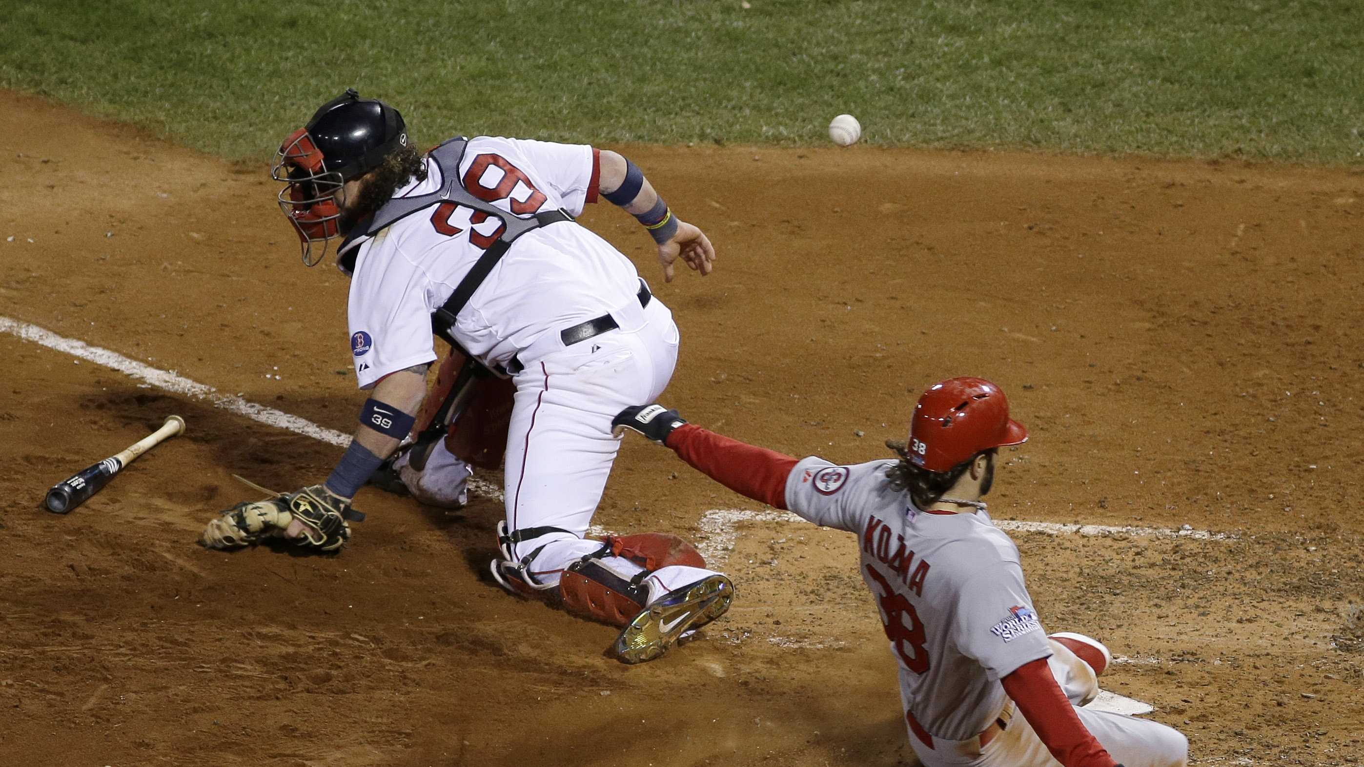 St. Louis Cardinals' Pete Kozma scores on a sacrifice fly as Boston Red Sox catcher Jarrod Saltalamacchia can't handle the throw during the seventh inning of Game 2 of baseball's World Series Thursday, Oct. 24, 2013, in Boston.