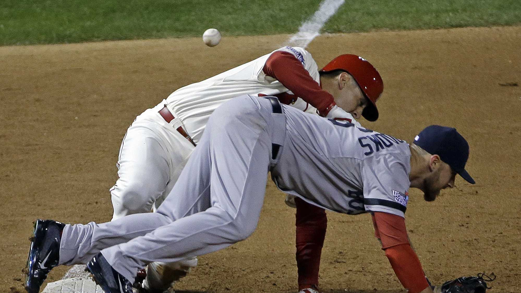 St. Louis Cardinals' Allen Craig gets tangled with Boston Red Sox's Will Middlebrooks during the ninth inning of Game 3 of baseball's World Series Saturday, Oct. 26, 2013, in St. Louis. Middlebrooks was called for obstruction on the play and Craig went in to score the game-winning run. The Cardinals won 5-4 to take a 2-1 lead in the series.