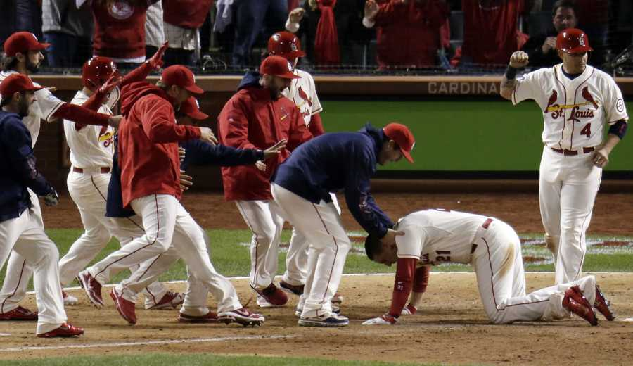 Teammates mob St. Louis Cardinals' Allen Craig at home after Craig scored the game-winning run on an obstruction call.