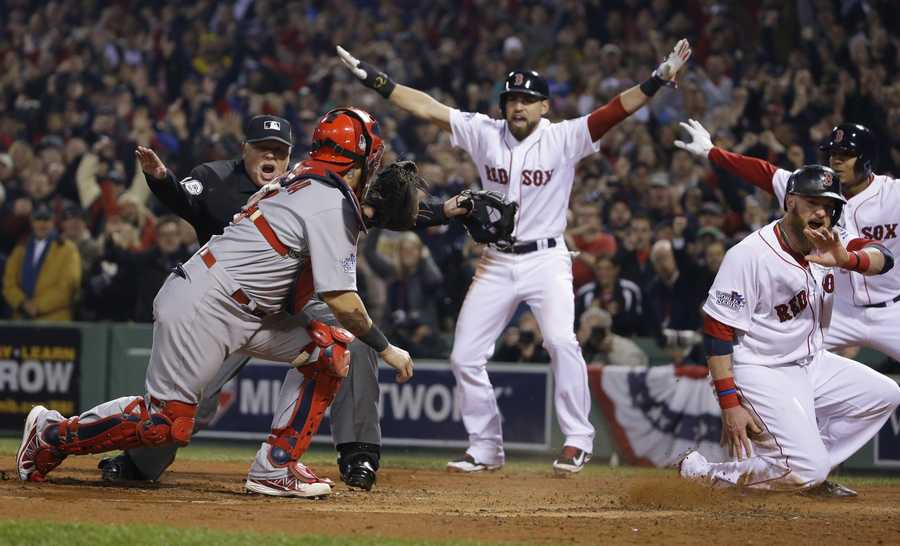 St. Louis Cardinals catcher Yadier Molina looks back as home plate umpire Adam Wainwright call Boston Red Sox's Jonny Gomes safe on a three run RBI double by Shane Victorino during the third inning of Game 6 of baseball's World Series Wednesday, Oct. 30, 2013, in Boston. At center is Jacoby Ellsbury.