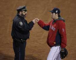 Boston police officer Steve Horgan, greets Boston Red Sox relief pitcher Junichi Tazawa as he walks to the bullpen during the third inning of Game 6 of baseball's World Series against the St. Louis Cardinals Wednesday, Oct. 30, 2013, in Boston.