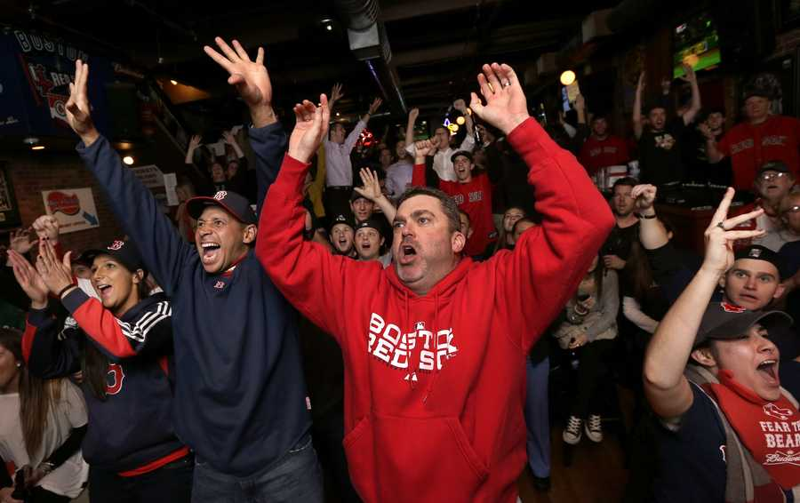Boston Red Sox fan George Moriarty, of Agawam, Mass., center, cheers with others in a bar near Fenway Park as the Red Sox score in the fourth inning of Game 6 of baseball's World Series against the St. Louis Cardinals on Wednesday, Oct. 30, 2013, in Boston.