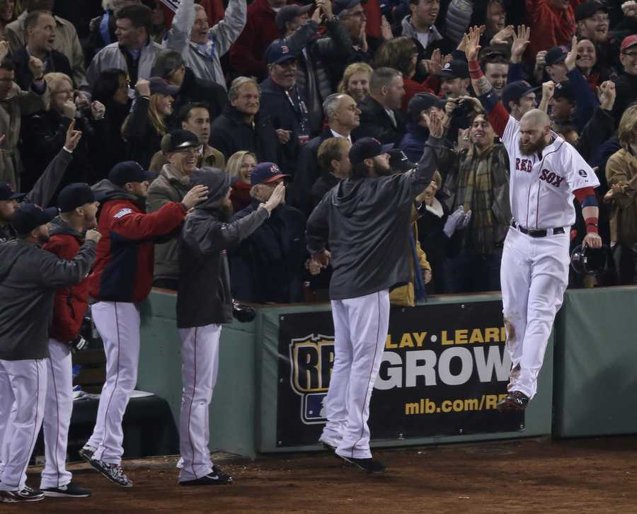 Boston Red Sox's Jonny Gomes celebrates with teammates after scoring during the third inning of Game 6 of baseball's World Series against the St. Louis Cardinals Wednesday, Oct. 30, 2013, in Boston.