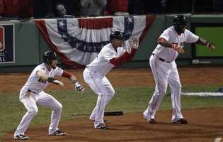 Boston Red Sox's Jacoby Ellsbury, left, Xander Bogaerts, middle, and David Ortiz, signal for Jonny Gomes to slide at home during the third inning of Game 6 of baseball's World Series Wednesday, Oct. 30, 2013, in Boston.