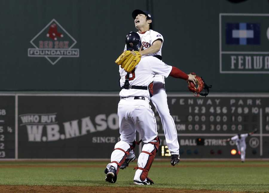 Boston Red Sox relief pitcher Koji Uehara and catcher David Ross celebrate after getting St. Louis Cardinals' Matt Carpenter to strike out and end Game 6 of baseball's World Series Wednesday, Oct. 30, 2013, in Boston. The Red Sox won 6-1 to win the series.