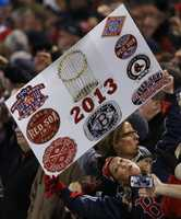 A fan poses with a makeshift championship poster during Game 6 of baseball's World Series between the St. Louis Cardinals and the Boston Red Sox Wednesday, Oct. 30, 2013, in Boston.