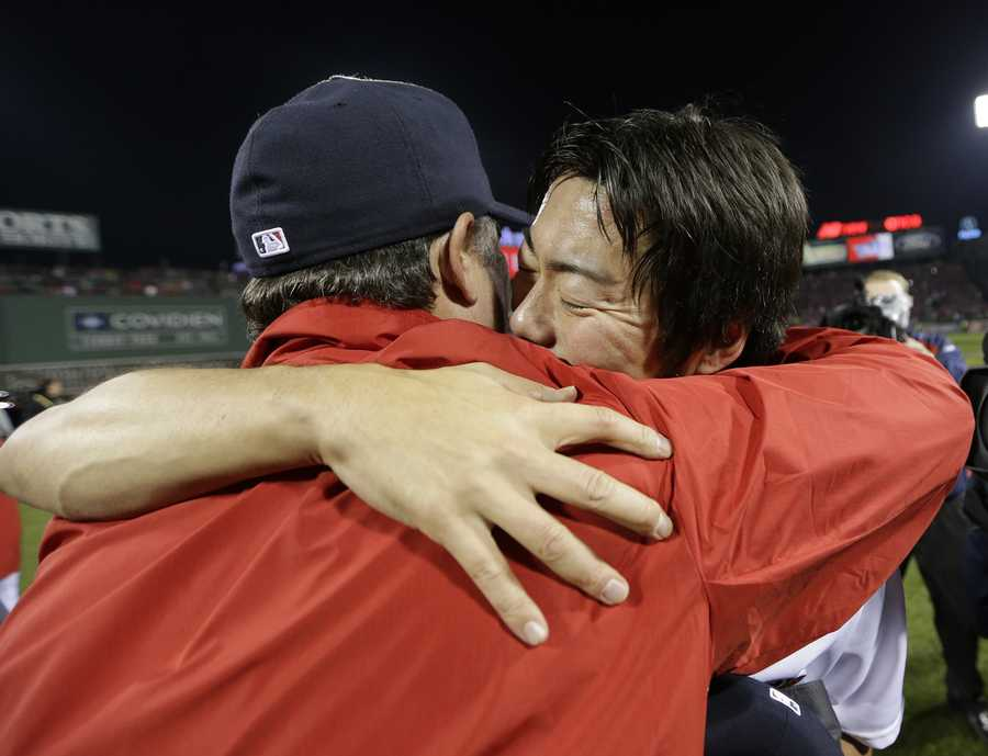 Boston Red Sox manager John Farrell hugs relief pitcher Koji Uehara after Boston defeated the St. Louis Cardinals in Game 6 of baseball's World Series Wednesday, Oct. 30, 2013, in Boston. The Red Sox won 6-1 to win the series.