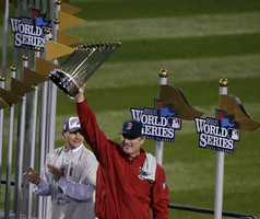 Boston Red Sox manager John Farrell holds up the championship trophy after Game 6 of baseball's World Series Wednesday, Oct. 30, 2013, in Boston. The Red Sox beat the St. Louis Cardinals 6-1 to win the series.