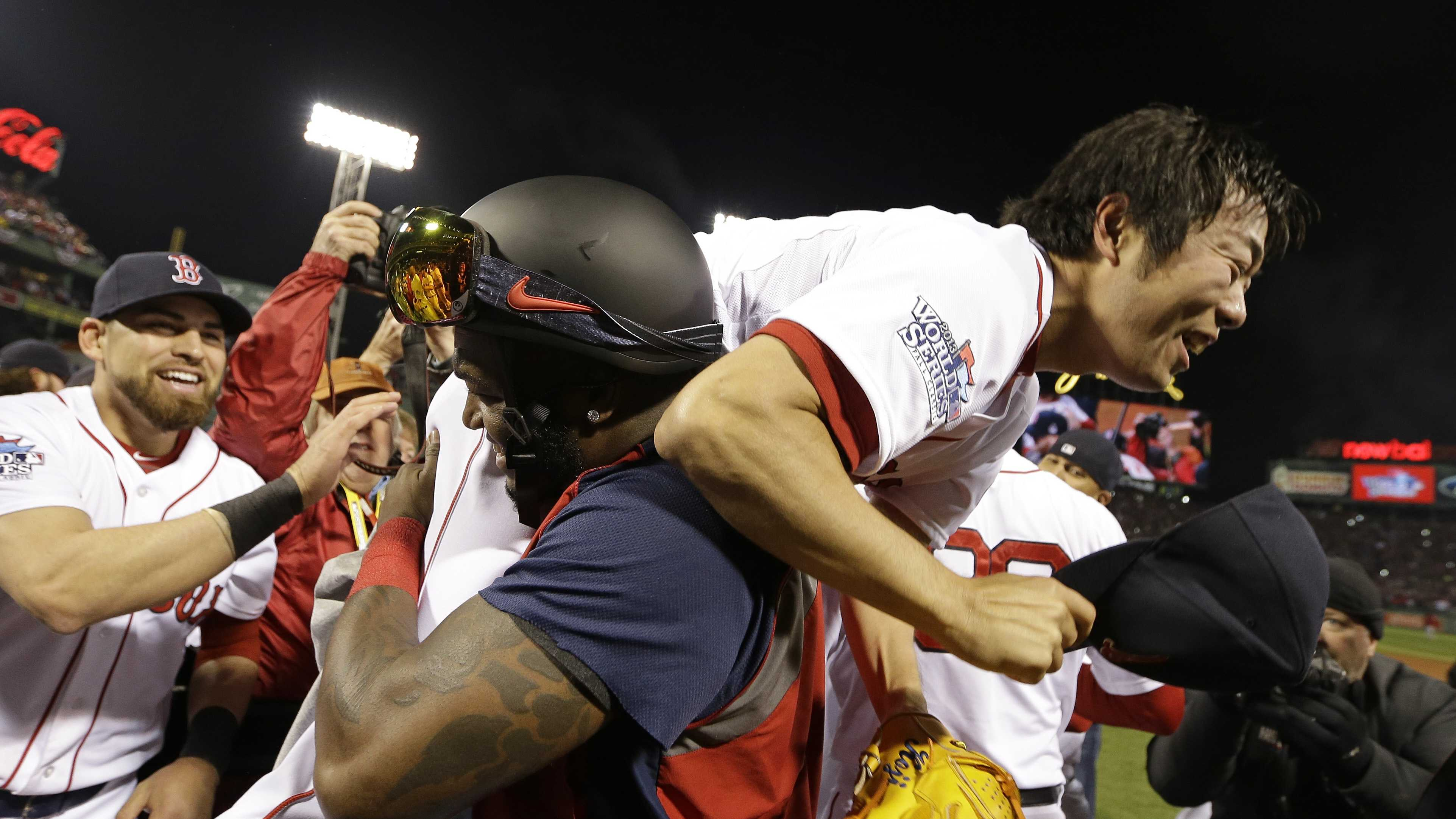 Boston Red Sox's David Ortiz lifts relief pitcher Koji Uehara after Boston defeated the St. Louis Cardinals in Game 6 of baseball's World Series Wednesday, Oct. 30, 2013, in Boston. The Red Sox won 6-1 to win the series.