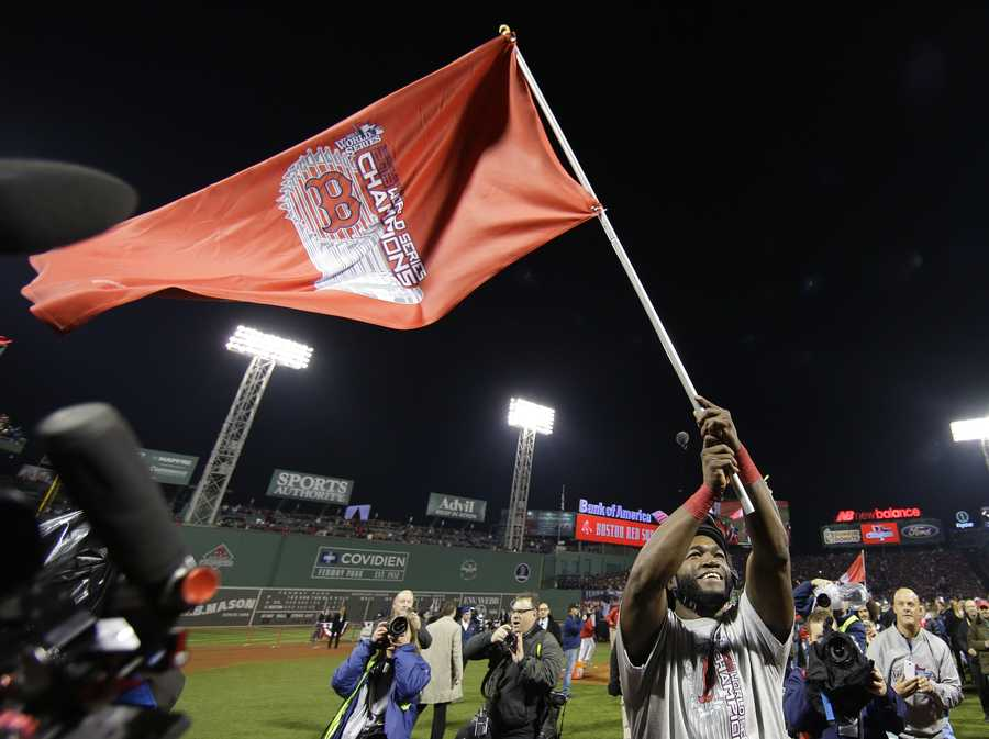 Boston Red Sox's David Ortiz waves a flag after Boston defeated the St. Louis Cardinals in Game 6 of baseball's World Series Wednesday, Oct. 30, 2013, in Boston. The Red Sox won 6-1 to win the series.