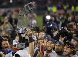 A player holds up the championship trophy after defeating the St. Louis Cardinals in Game 6 of baseball's World Series Wednesday, Oct. 30, 2013, in Boston. The Red Sox won 6-1 to win the series.