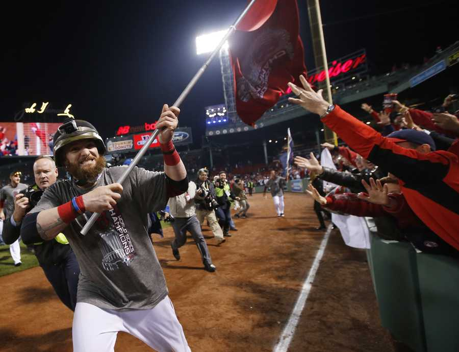 Boston Red Sox left fielder Jonny Gomes runs with a championship flag after defeating the St. Louis Cardinals in Game 6 of baseball's World Series Thursday, Oct. 31, 2013, in Boston. The Red Sox won 6-1 to win the series.