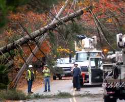 Police and Nstar crews work at the scene where a tree fell on live wires and snapped a utility pole on Long Pond Road in Plymouth.