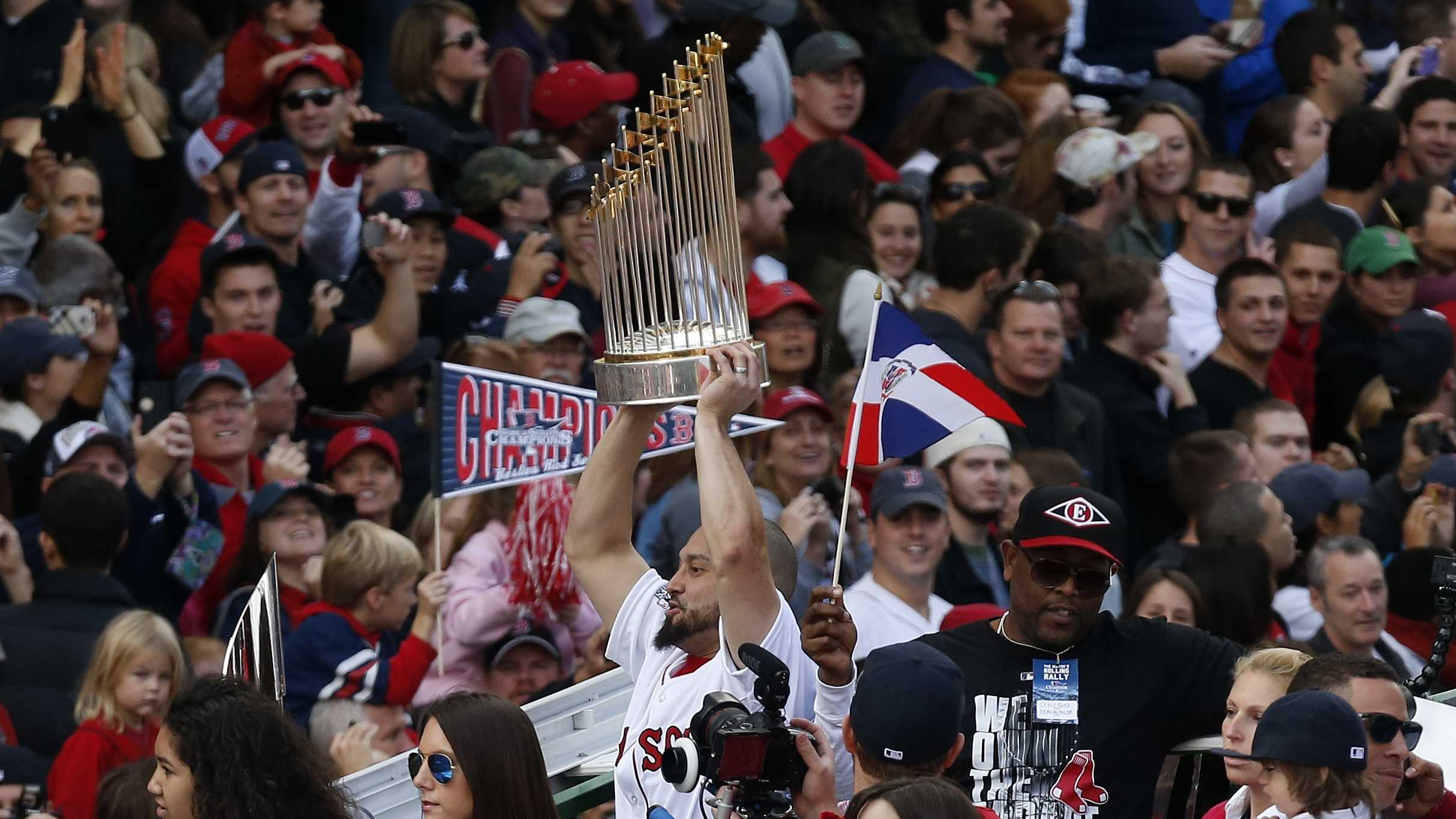 Boston Red Sox's Shane Victorino holds the World Series trophy from on Duck Boat during a victory parade celebrating the team's third World Series title since 2004, Saturday, Nov. 2, 2013, in Boston.