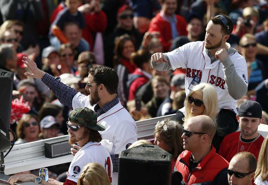 Boston Red Sox's Clay Buchholz, left, John Lackey, second from left, and Daniel Nava, top right, wave from a Duck Boat during a victory parade celebrating the team's third World Series title since 2004, Saturday, Nov. 2, 2013, in Boston.