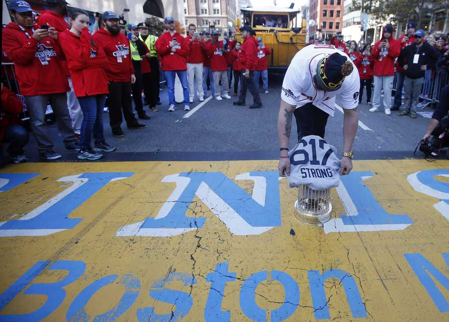Boston Red Sox's Jonny Gomes places the championship trophy and a Red Sox baseball jersey at the Boston Marathon Finish Line during a pause in their World Series victory rolling rally in Boston, Saturday, Nov. 2, 2013, to remember those affected by the Marathon bombing.