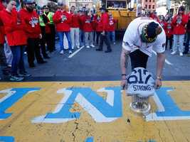 Boston Red Sox's Jonny Gomes places the championship trophy and a Red Sox baseball jersey at the Boston Marathon Finish Line during the rolling on Nov. 2, 2013, to remember those affected by the Marathon bombing.