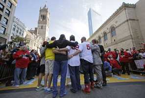 Boston Red Sox's Jonny Gomes (5) and Jarod Saltalamacchia (39) embrace at the finish line of the Boston Marathon, with people affected by the April 2013 bombings, during a parade in celebration of the baseball team's World Series win, Saturday, Nov. 2, 2013, in Boston.