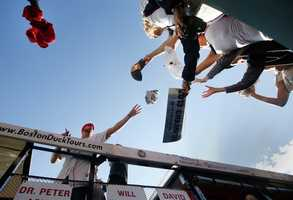 Fans at Fenway Park reach out to Boston Red Sox's Will Middlebrooks, left, who stands in a duck boat ready to celebrate their World Series baseball championship in a rolling rally in Boston, Saturday, Nov. 2, 2013.