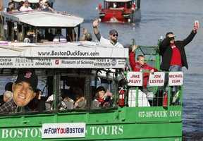 Boston Red Sox's Jon Lester, top center, and Jake Peavy, right, wave from a duck boat on the Charles River during a rolling victory parade celebrating the baseball team's World Series title, Saturday, Nov. 2, 2013, in Boston.