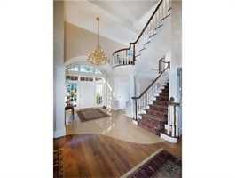 Its gracious entrance is welcomed by a coffered ceiling fireplaced living room open to a fireplaced dining room.