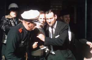 Oswald being led out from the Texas Theatre by Dallas Police.