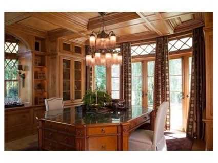 Ahandsome wood paneled study has floor to ceiling French doors that lead to a small covered terrace and overlook the homes well landscaped grounds.