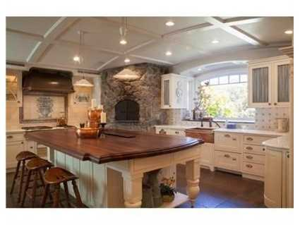 Boasting a generous Chef's kitchen with a large Mahogany island, marble counters, top-of-the-line appliances, a custom built wood burning pizza oven, walk in pantry & a small office.