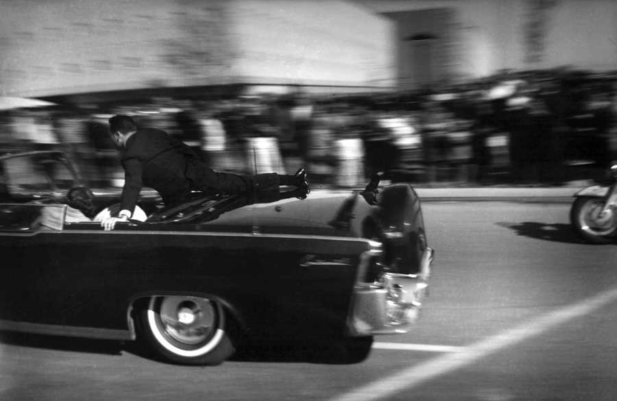 The limousine carrying mortally wounded President John F. Kennedy races toward the hospital seconds after he was shot in Dallas. Secret Service agent Clinton Hill is riding on the back of the car, Nellie Connally, wife of Texas Gov. John Connally, bends over her wounded husband, and first lady Jacqueline Kennedy leans over the president.