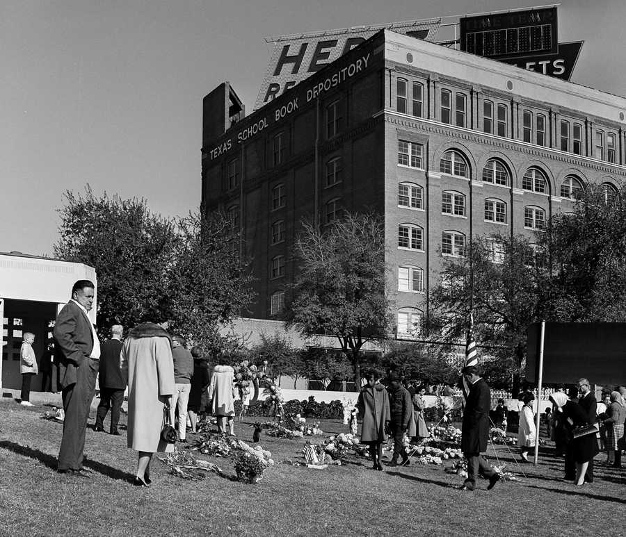 In this November 1963 file photo, mourners leave flowers on the lawn near the Texas Book Depository after the assassination of President John F. Kennedy in Dallas.