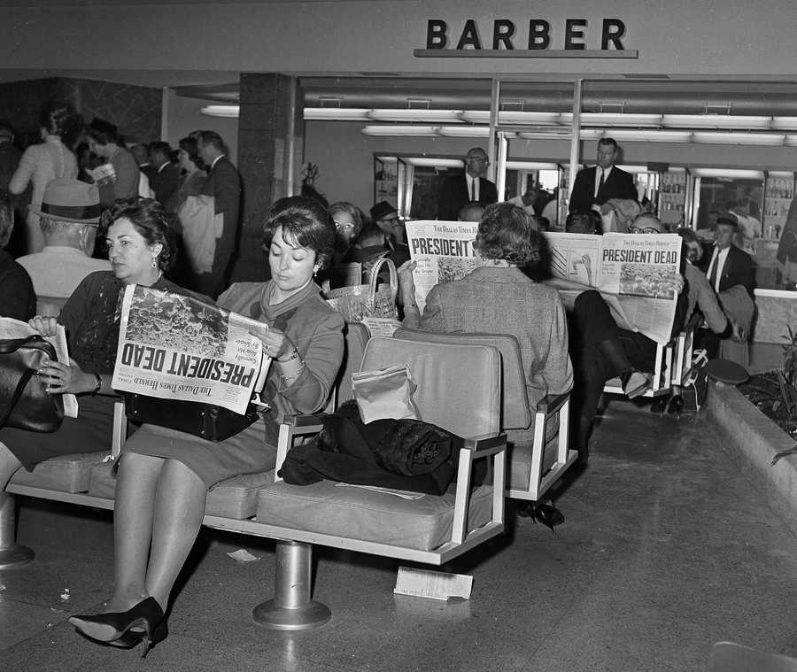 In this Nov. 23, 1963 file photo, people waiting for flights from Dallas at Love Field read the news of President John F. Kennedy's assassination in the Dallas Times Herald newspaper.